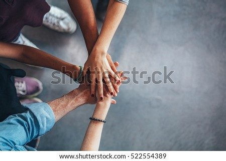 Cropped image of young people\'s hands on top of each other. Top view of young group with hands on stack.