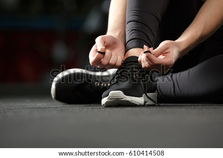 Shutterstock Cropped image of young strong fitness lady sitting and tie laces in gym.