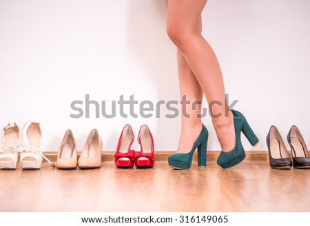 Cropped image of young woman in high heeled shoes standing against the wall while more shoes laying in a row near her