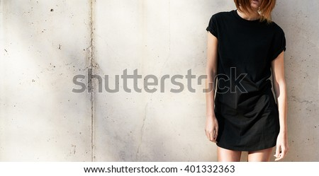 Cropped image on a stylish young woman dressed in a black blank t-shirt standing against a background of a concrete wall in the rays of the setting sun #401332363