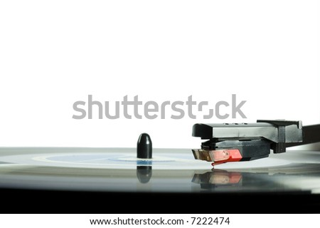 Cropped image shot directly from above of a record player needle, with LP underneath