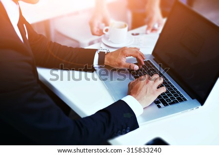 Cropped image view of man\'s hands in elegant suit keyboarding on laptop computer with blank copy space screen for your advertising content or text message, man working on net-book in a cafe, flare sun