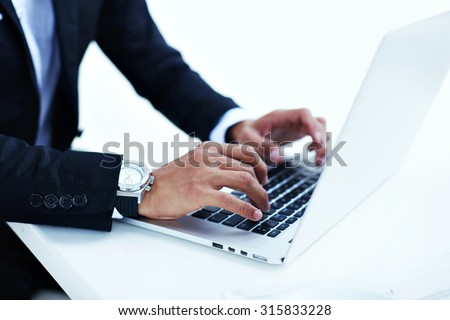 Cropped image view of wealthy successful man working on his laptop at coffee shop, entrepreneur or businessman\'s hand busy using net-book,male person in luxury watches typing text message on computer