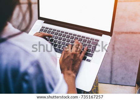 Photo of Cropped image view of woman's hands are typing text message on keyboard of net-book while sitting in modern coffee shop. Young student girl is connecting to sidewalk cafe wireless via laptop computer