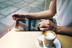 Cropped image with woman's hands touching screen of digital tablet at the table with cup of coffee