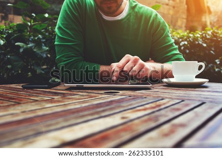 Cropped image young man sitting at the table with cup of coffee, digital tablet and smart phone, man's hands typing message on touch screen tablet while sitting on balcony terrace, flare sun