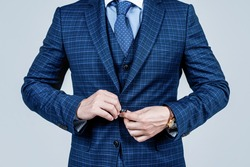 cropped man buttoning up male vested blue suit jacket with tie in formal fashion style, formalwear