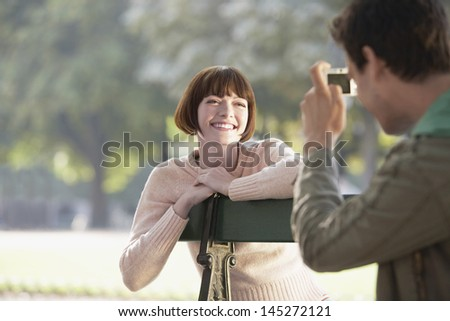 Cropped man photographing smiling young woman on bench