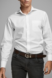 Cropped medium full shot of a young man dressed in a white buttoned shirt with a pocket and gray jeans with a belt. The brown belt is made of glossy perforated leather and equipped