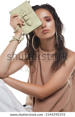 Cropped medium shot of a young dark-haired lady in a beige blouse hiding her face behind an olive-green textured leather clutch with a long handle and a flap fastening decorated with belt and buckle. #1544290193