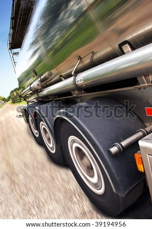 Cropped, motion-blurred, tilted close-up of semi on the road. No people are viewable in the shot. Vertically framed shot. - stock photo