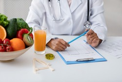 Cropped of african american female nutritionist filling medical chart, working at clinic, having fresh juice and bowl with fresh fruits and vegetables