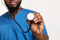 Cropped of black male therapist using stethoscope, checking on patient lungs, white studio background, copy space