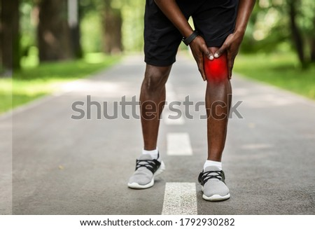 Cropped of black sportsman touching his inflamed knee highlighted with red, park background, copy space Stockfoto ©