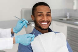 Cropped of dentist tools in doctor hands and cheerful african guy in dentist chair