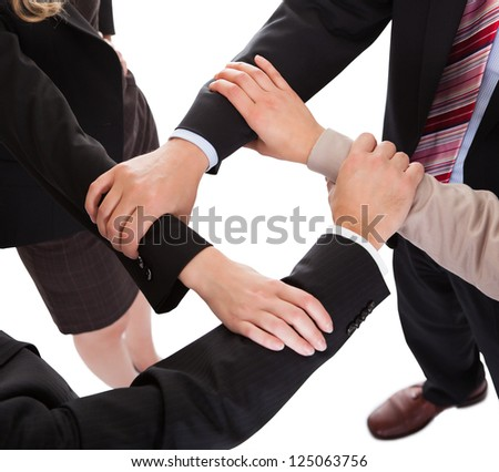 Cropped overhead view of a diverse group of businesspeople linking hands in a team