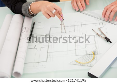 Cropped overhead view of a male and female architect discussing a set of blueprints spread out on a table