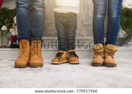 Cropped parents little son legs Child boy in sweater yellow boots staying porch snow steps at light house with decorated New Year home. Christmas good mood. Family on holiday 2019. Bottom view mockup.