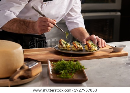 Cropped photo Close-up hands of male cook adding greens finishing dish, decorating meal in the end. gastronomy, food, nutrition, cafe concept Stok fotoğraf ©
