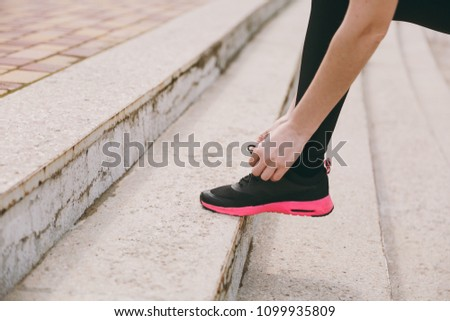 Cropped photo close up of female hands tying shoelaces on woman black and pink sneakers on training on stairs outdoors. Fitness, healthy lifestyle concept. Copy space for advertisement