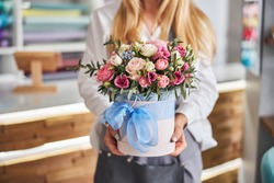 Cropped photo of a blonde lady holding a cylinder box of various flowers while standing in a floral studio