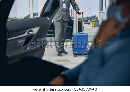 Cropped photo of a Caucasian man in a face mask waiting for his private driver Photo stock ©