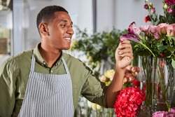 Cropped photo of a joyful floral artist wearing an apron with stripes while examining the condition of a purple flower