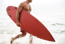 Cropped photo of a serious strong handsome man surfer with surfing on a beach outside.