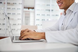 Cropped photo of a smiling male optician in a lab coat working on his computer