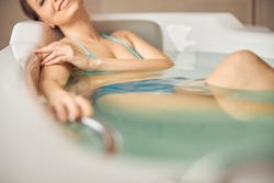 Cropped photo of a smiling young female in a bikini taking a soothing hot bath