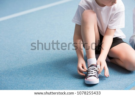 Cropped photo of a young boy tying his sports shoes on the court #1078255433