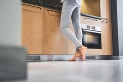 Cropped photo of a young housewife in denim pants standing barefoot on the tile floor