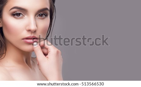 Cropped photo of beautiful sexy model showing her perfect skin face with natural shiny make up and full glossy lips. Skincare, cosmetics. Glamorous fashion beauty look. Isolated, gray copy space  #513566530