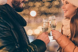 Cropped photo of charming couple toast champagne alcohol glass, newyear congratulation outdoors on evening x-mas street