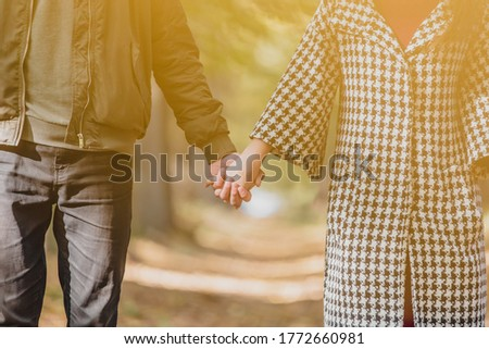 Cropped photo of couple in love holding hands in autumn nature with sunrays everywhere.