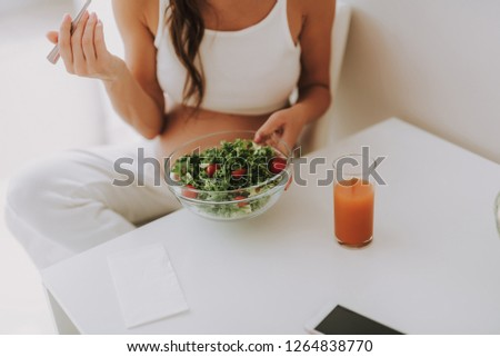 Cropped photo of future mama tasting salad and holding big glass bowl in hands while sitting behind kitchen table #1264838770