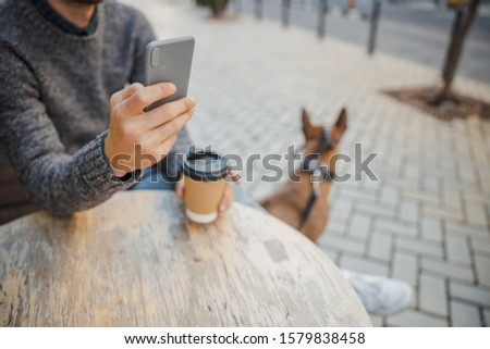 Cropped photo of pet owner sitting at the cafe table outdoors and using a modern phone #1579838458