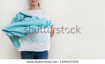 Cropped photo of positive and cheerful lady with plastic laundry basket in hands. She standing against wall inside flat with bright interior and making nice smile #1344635504