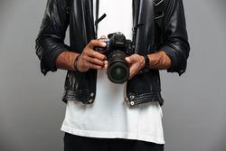 Cropped photo of stylish afro american guy holding digital camera, isolated on gray background