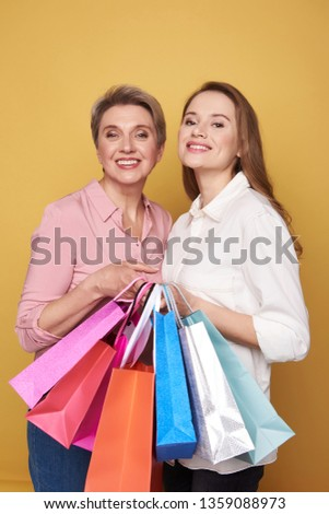 Cropped photo of stylish ladies wearing fashionable blouses and making shopping. They are posing on yellow background with colorful paper bags in arms. Black friday sale concept