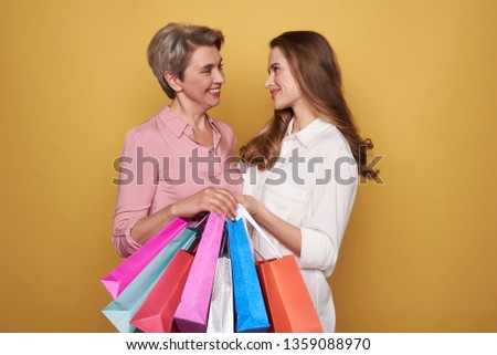 Cropped photo of stylish ladies wearing fashionable blouses and making shopping. They are talking against yellow background with colorful paper bags in arms. Black friday sale concept