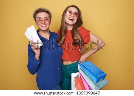Cropped photo of stylish smiling ladies wearing fashionable blouses after shopping. Pretty daughter holding colorful paper bags in arm while her cheerful mother keeping two tickets against orange