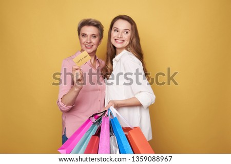 Cropped photo of stylish smiling ladies wearing fashionable blouses and holding colorful paper bags in arms. Charming mother is keeping a gold card in hand. Black friday sale concept