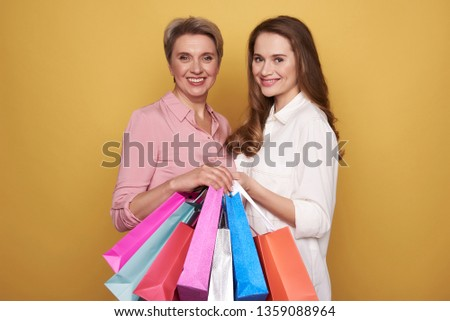 Cropped photo of stylish smiling ladies wearing fashionable blouses and making shopping. They are posing against yellow background with colorful paper bags in arms. Black friday sale concept