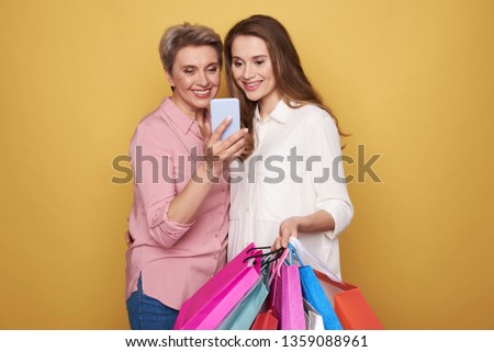 Cropped photo of stylish smiling ladies wearing fashionable blouses. They are making selfie while holding colorful paper bags in arms against yellow background . Black friday sale concept