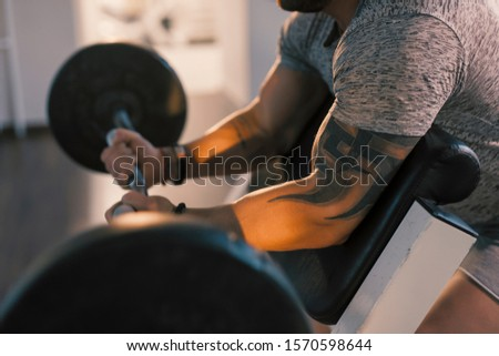 Cropped photo of the male hands lifting barbell in a gym on EZ bar preacher curl, biceps exercise