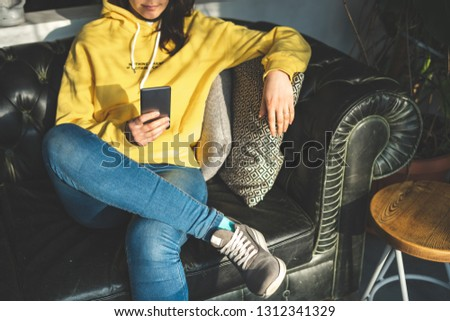 Cropped photo of unrecognizable lady person in stylish denim jeans. She sitting inside loft interior space in restaurant and holding portable telephone equipment in hands #1312341329