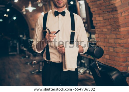 Shutterstock Cropped photo of young guy with bristle in a barber shop, standing with straight razor and towel in his hands, dressed classy in a retro style, ready to do styling