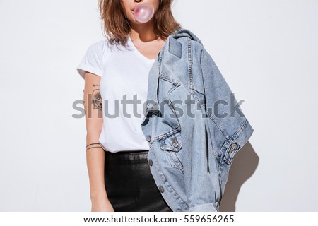 Cropped photo of young lady dressed in jeans jacket standing isolated over white background while blowing bubble with chewing gum.