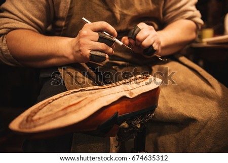 Cropped photo of young man shoemaker at footwear workshop. #674635312